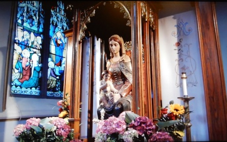 Life-size statue of the Blessed Mother with toddler Jesus on her lap encased in wood-and-glass